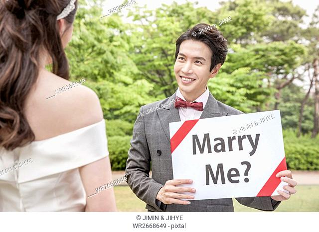 Portrait of young smiling broom holding English message looking at his bride outdoors