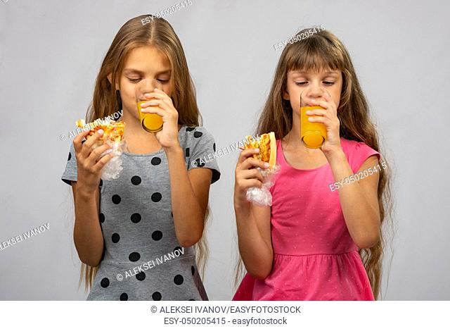 Two girls drink juice and eat a bun