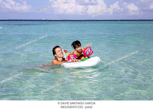 Maldives, Gulhi, mother and daughter playing with an inflatable airbed in shallow water