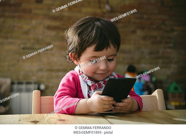 Baby girl using mobile phone at home