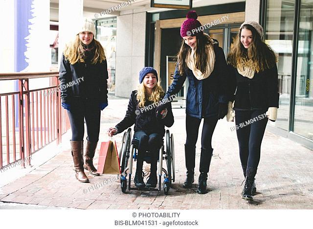 Girls walking and using wheelchair on sidewalk