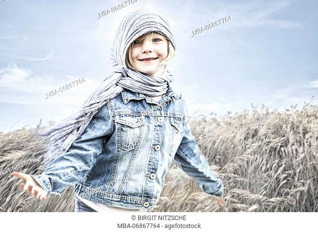 Little girl standing in a cornfield, against the wind
