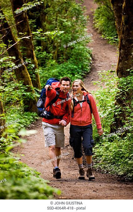 Portland, Oregon, USA, Couple walking on trail through forest