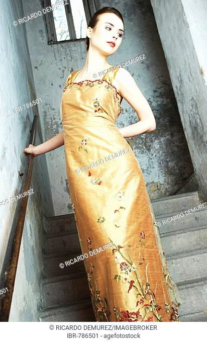Young woman dressed up in an evening dress, evening gown standing on a staircase
