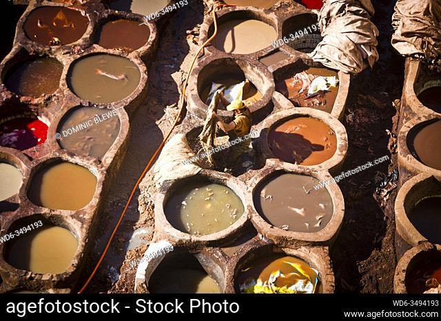 A worker dyes leather in a vat of dye in the Tanners Quarter of Fes, Morocco