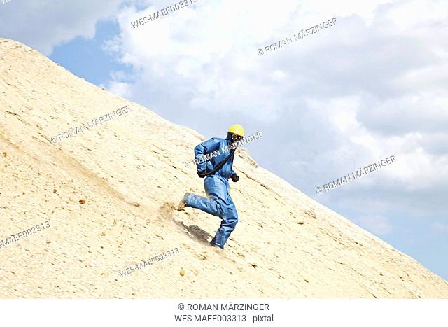 Germany, Bavaria, Man in protective workwear running on slope of sand dune