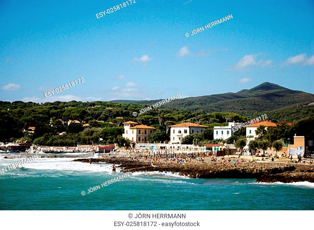 Italian coastal holiday village with rocks, beach and forested hills in background. Strada del Vino Costa degli Etruschi, Italy