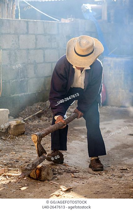 Guatemala, Poaquil, Mayan man chopping wood