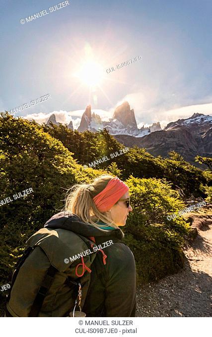 Female hiker hiking near sunlit Fitz Roy mountain range in Los Glaciares National Park, Patagonia, Argentina