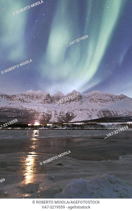The Northern Lights and starry sky reflected in the frozen sea Nordkjosbotn Lyngen Alps Tromsø Norway Europe
