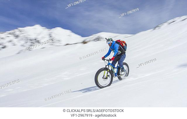 Snow, descend, fat bike. Fat bike in descend from Casati Refuge in Valfurva, Valtellina, Lombardy, Italy