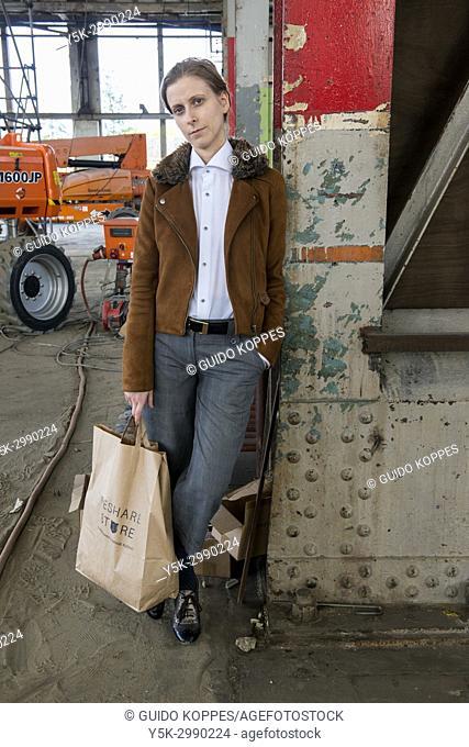 Tilburg, Netherlands. Portrait gender biased woman, wearing men's fashion inside an abandoned industrial environment. Wearing opposite gender's wardrobe defines...