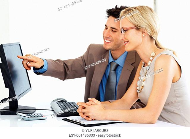 Happy business man with female colleague pointing at computer screen while preparing project