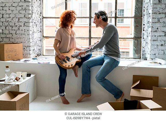 Couple moving into industrial style apartment, sitting on window ledge with guitar