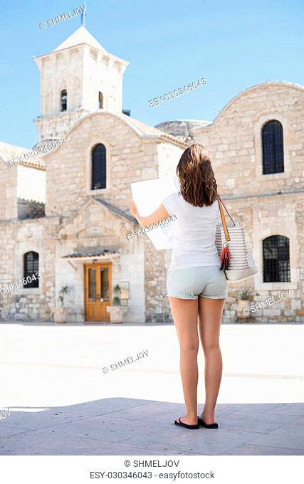 Teenage girl with a map on a city tour. Young and beautiful woman have a weekend in Larnaca. Vacation, holidays and traveling concept