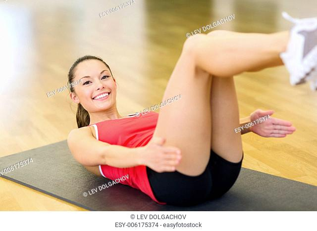 fitness, sport, training, gym and lifestyle concept - smiling woman doing exercise on mat in gym