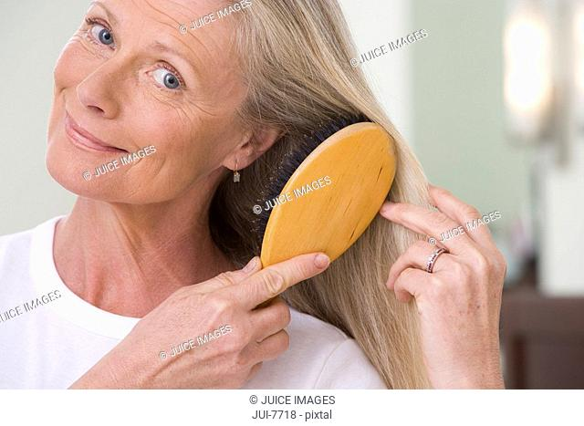 Senior woman brushing long, straight hair with hairbrush in bathroom, smiling, close-up, front view, portrait