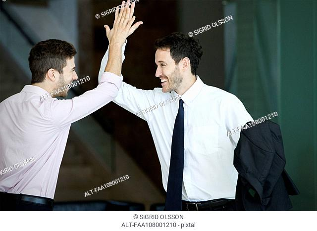 Business colleagues exchanging high five