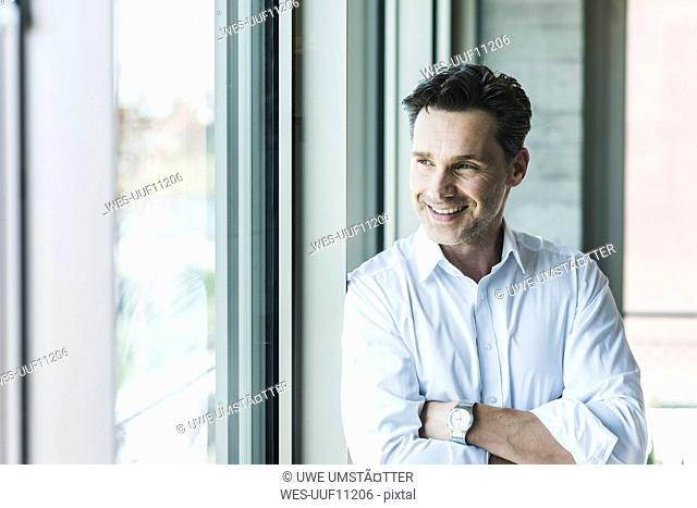 Portrait of confident businessman looking through window