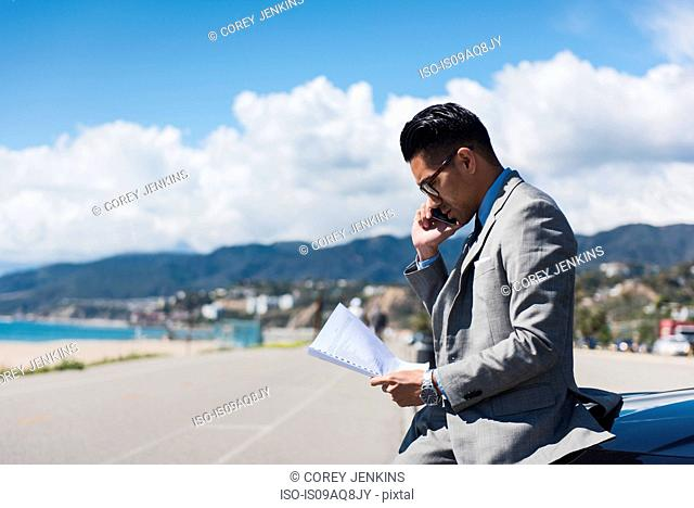 Young businessman sitting on car hood at coastal parking lot talking on smartphone