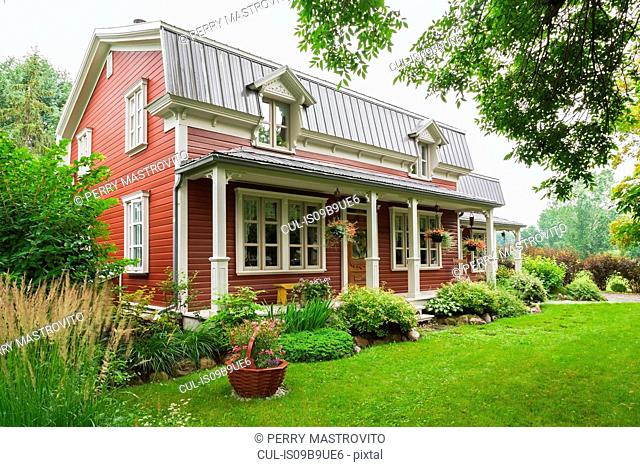Pinewood plank house facade with mansard roof and landscaped garden, Quebec, Canada