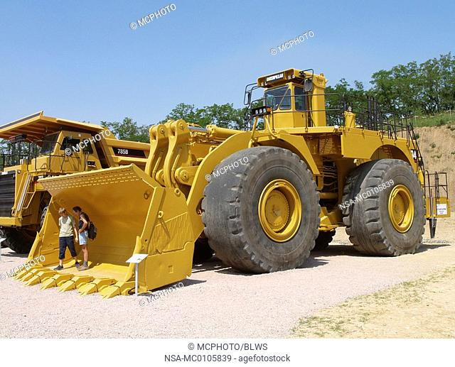 persons standing in the big excavator shovel of an excavator for surface mining