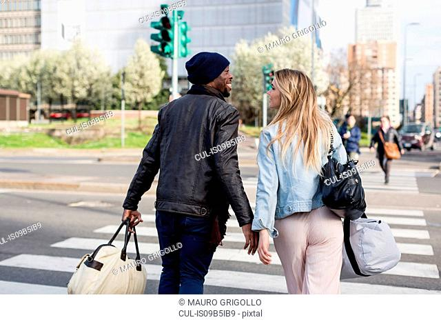 Young couple crossing road, carrying holdalls, rear view, smiling