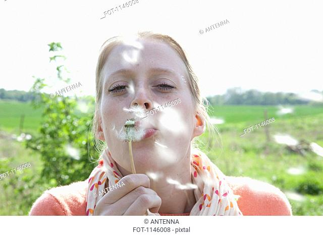 A woman blowing on a dandelion, close-up