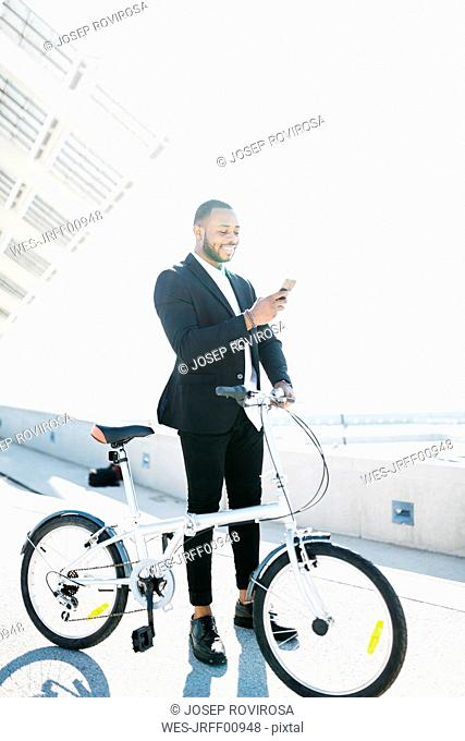 Smiling businessman with bicycle looking at cell phone