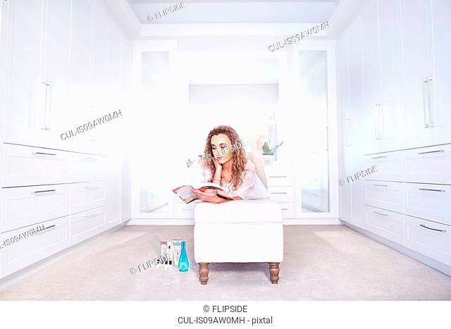 Young woman lying on ottoman reading a book in bedroom