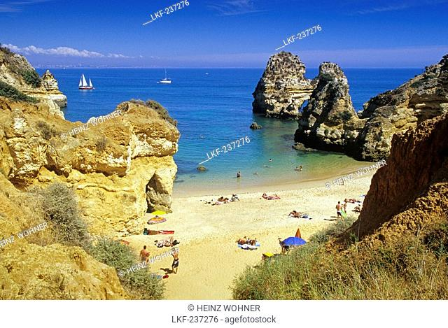View at people on the beach at the rocky coast, Praia do Camilo, Algarve, Portugal, Europe