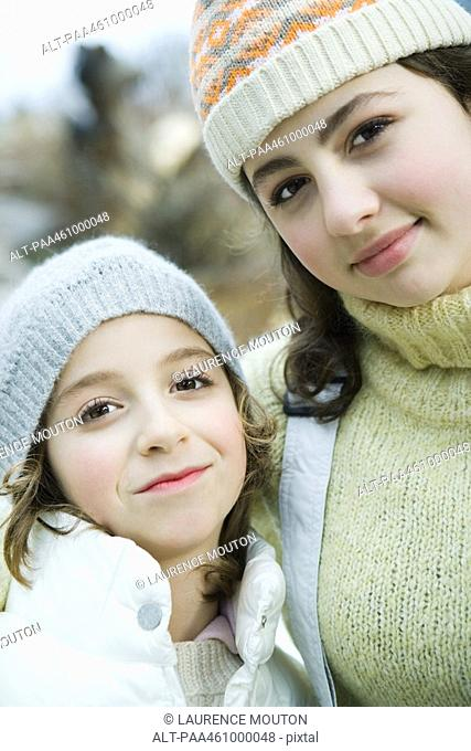 Two sisters smiling at camera, wearing knit hats, portrait