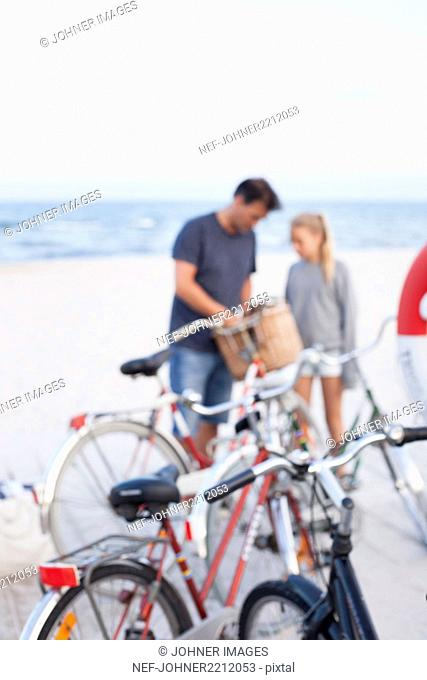 Bicycles on beach, father with daughter on background