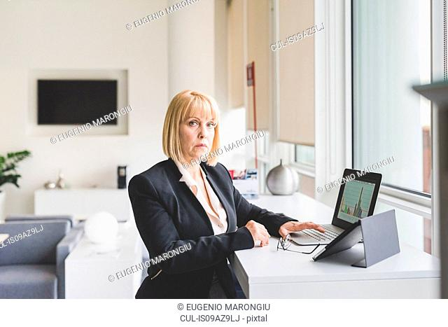 Portrait of mature businesswoman using digital tablet and laptop at office desk