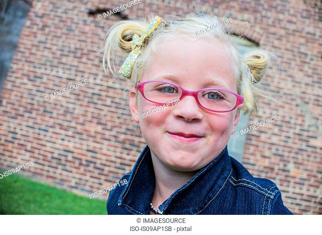 Portrait of young girl wearing pink glasses