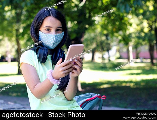 Girl with face mask using smart phone in public park