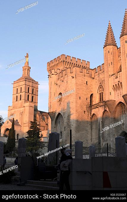The pink lit forms of the papal palace pinnacles and towers and the golden madonna of the cathedral are repeated below in the grey clad cafe parasols, Avignon