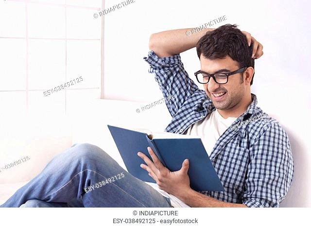 Smiling young man reading book