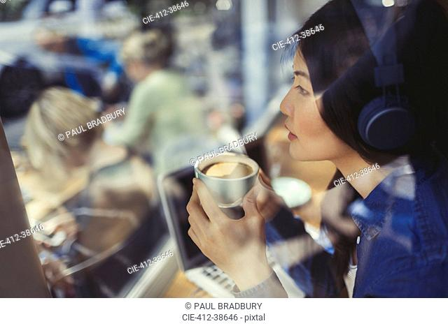 Pensive young woman listening to music with headphones and drinking coffee at cafe window