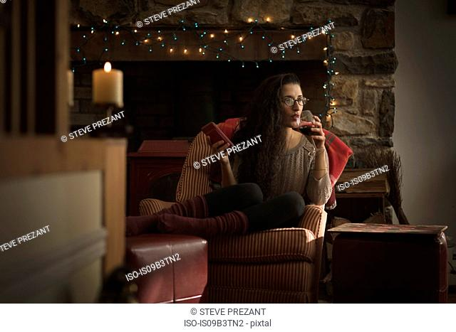 Young woman relaxing in armchair drinking red wine