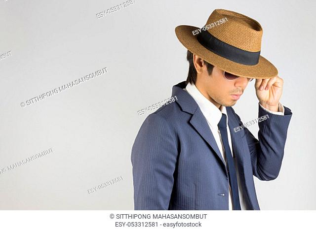 Young Asian Portrait Businessman in Navy Blue Suit Wear Hat and Touch Sunglasses at Right Frame on Grey Background