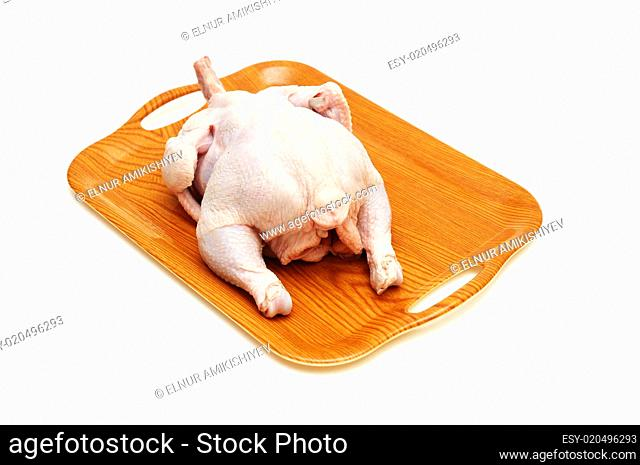 Raw chicken in the wooden tray isolated on white