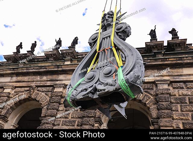 15 July 2021, Saxony, Dresden: 20210715-SN-Dresden-Semperoper - Lyre secured with ropes hovers in the air. In the picture background the sandstone sculptures of...