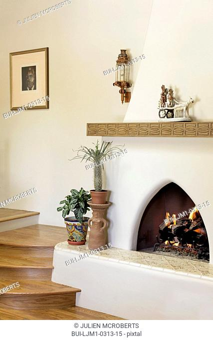 Lit fireplace with wooden stairs at home; Santa Fe; New Mexico; USA