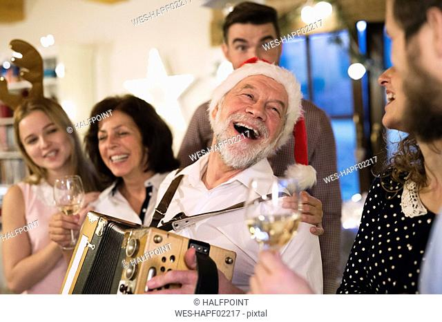 Senior man playing accordion for happy family at Christmas