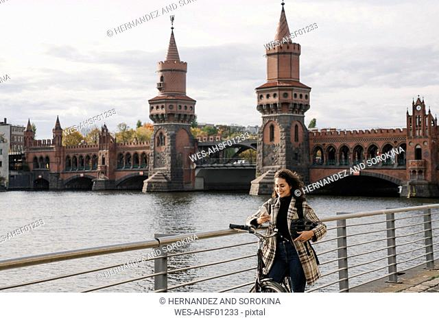 Smiling woman with bicycle and smartphone in the city at Oberbaum Bridge, Berlin, Germany