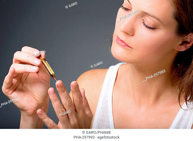 Woman holding glass ampoule of vitamin D