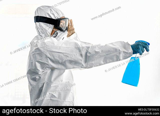 Woman wearing protective clothes, sanitizing her home