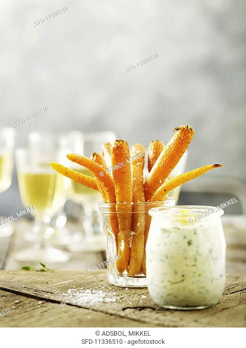 Roasted carrots in a glass with a dip