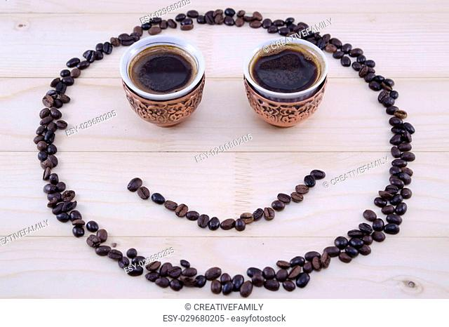 Smiley made out of coffee grains and two vintage cups of coffee as eyes